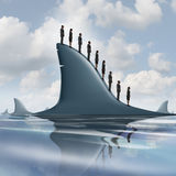 Concept Of Risk. Business metaphor as a group of courageous or unaware businesspeople standing on the dorsal fin of a giant shark as a symbol for overcoming Stock Images