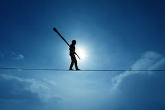 Concept of risk taking and challenge highline walker in blue sky Stock Image