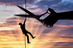 Concept of risks in business. Silhouette of a businessman climbs on a tightrope and a hand with scissors intends to cut a rope. Concept of risks in business Stock Image