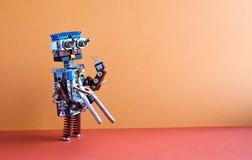 Concept robotique de service de fixation de réparation d'entretien Bricoleur de robot avec des pinces Mur de Brown, fond rouge de photographie stock