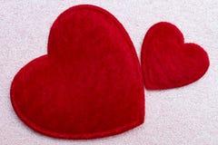 Concept Romance : Deux coeurs pelucheux rouges au-dessus de fond rose de scintillement Photos libres de droits