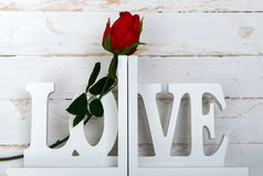 Concept romantic, one rose with wooden white love. Concept romantic, one rose with a wooden white love Stock Image