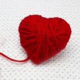 Concept romantique de jour de Noël ou de valentines Boule rouge de fil comme un coeur sur le fond blanc de crochet Coeur rouge fa Image libre de droits