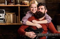 Concept romantique de soirée Madame et l'homme avec la barbe sur les visages heureux étreint et joue la guitare Couples dans le v Photo stock