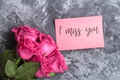 Concept romantique Roses rouges et inscription tu me manque sur un fond concret gris photos libres de droits