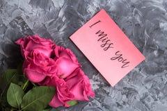 Concept romantique Roses rouges et inscription tu me manque sur un fond concret gris photographie stock libre de droits