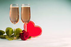 Concept with the rose, with heart relating to glasses of champagne Stock Photos