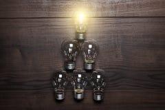 Concept rougeoyant de direction d'ampoule sur en bois Photographie stock libre de droits