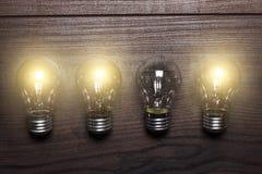 Concept rougeoyant de point faible d'ampoules sur en bois Images libres de droits