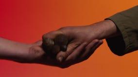Concept ruilhandel voorraad Het concept ruilhandel en vertrouwen: de menselijke hand die een hulpmiddel in de hand van een andere stock video