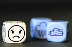 Concept of sad autumn weather - emoticon and weather dice on bla. Ck background - stock photo Stock Images