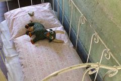 Concept of sad and poor childhood. Concept of a sad and poor childhood. Worn old handmade stuffed animal lying on a small rickety bed in a somber room Stock Photo