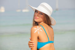 Concept for safe sunbathing, woman with sun cream. And hat Royalty Free Stock Image