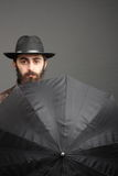 Concept of safety. Man with beard, in hat and with umbrella Stock Images