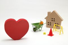 Concept of safety image. Red heart shaped wood, house and construction tools of miniature on white back ground. royalty free stock photography