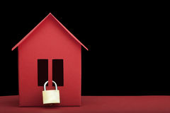Concept - Safety real estate. Red paper house on dark background. Clouseup Stock Images