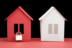 Concept - Safety real estate. White and red paper houses on dark background Royalty Free Stock Photography