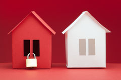 Concept - Safety real estate. White and red paper houses on red background Royalty Free Stock Photography