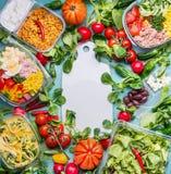 Concept sain de consommation avec de divers gamelles et ingrédients de salade de régime autour de la planche à découper blanche,  images stock