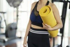 Concept sain de durée Tapis jaune de yoga de participation de jeune femme, dynam photos stock