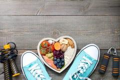 Concept sain de mode de vie avec la nourriture dans des accessoires de forme physique de coeur et de sports Image stock