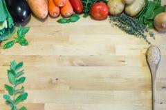 Concept sain de nourriture avec des légumes, des herbes et la cuillère sur le fond en bois Images libres de droits