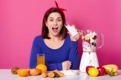 Concept sain de nourriture Fermez-vous d'une jeune femme épuise des baies et des bananes pour faire le smoothie Studio rose again photo libre de droits