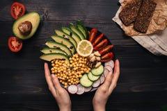 Concept sain de nourriture Mains tenant la salade saine avec le pois chiche image stock