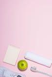 Concept sain Espadrilles, thé, pomme et bande de mesure sur le pastel Photos stock