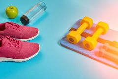 Concept sain, plan de régime avec les chaussures de sport et la bouteille de l'eau et d'haltères sur le fond bleu, nourriture sai Image stock