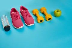 Concept sain, plan de régime avec les chaussures de sport et la bouteille de l'eau et d'haltères sur le fond bleu, nourriture sai Images stock