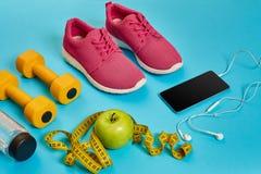 Concept sain, plan de régime avec les chaussures de sport et la bouteille de l'eau et d'haltères sur le fond bleu, nourriture sai Photographie stock libre de droits