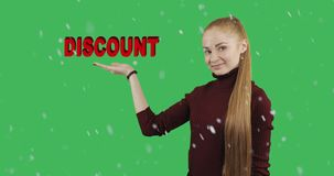 Concept of sale. Concept of discount. Pretty woman with long red hair shows her hand a symbol of the discount in snowy weather on green chroma key background stock video footage