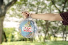 Young woman with earth globe and plastic bag royalty free stock photo