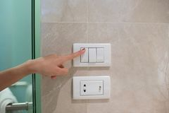 Woman hand turning off switch. Concept save energy. woman hand turning off switch royalty free stock photo