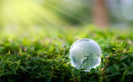 Concept Save the world save environment The world is in the grass of the green bokeh background royalty free stock photos