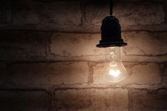 The concept of saving electricity or background in a dark key similar to the basement. A switched on light bulb shines next to a b. Rick wall. Free space royalty free stock images