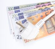 Concept of saving electricity at home. Euro banknotes and plug. Euro currency and plug. Concept of saving electricity at home Royalty Free Stock Photos
