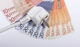 Concept of saving electricity at home. Euro banknotes and plug. Euro currency and plug. Concept of saving electricity at home Stock Image