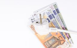 Concept of saving electricity at home. Euro banknotes and plug. Euro currency and plug. Concept of saving electricity at home Stock Photo