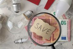 The concept of saving electricity. money and different bulbs close-up with the inscription save. Euro royalty free stock images