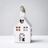 Concept for saving for a house, mini house with $1 poking out Stock Photo