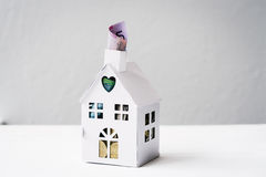 Concept for saving for a house, mini house with $5 poking out Royalty Free Stock Images