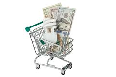 Concept: saving money on electricity. Energy saving lamp in a supermarket trolley and an image of dollars. Concept: saving money on electricity. Isolated on Stock Photo