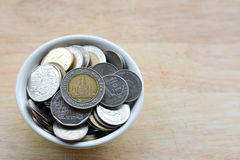 Concept of saving money. Putting coins in a cup on a wooden floor Stock Photos