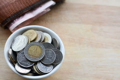 Concept of saving money. Putting coins in a cup on a wooden floor Stock Photography
