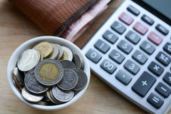 Concept of saving money. Putting coins in a cup on a wooden floor Royalty Free Stock Photography