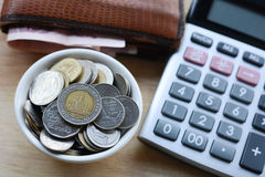 Concept of saving money. Putting coins in a cup on a wooden floor royalty free stock image