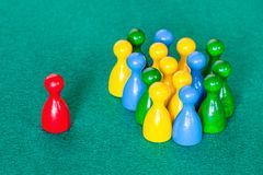 One red pawn in front of many various pawns stock photography
