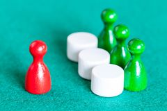 One red pawn in front of three green pawns royalty free stock photo